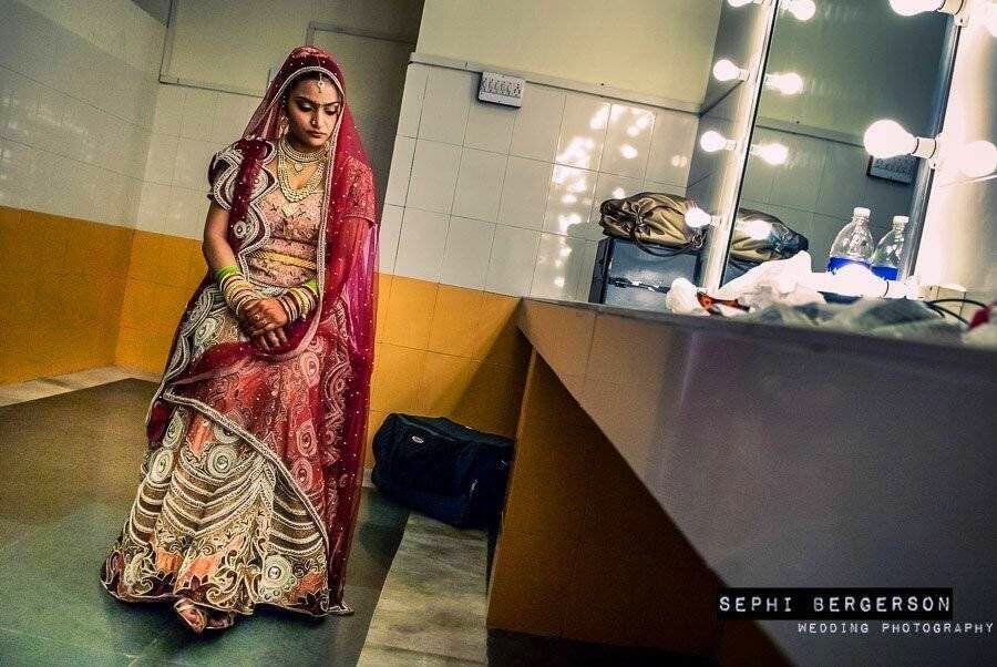 A quiet moment in the dressing room. A Rajput bride just before the wedding ceremony. Rajputs are instructed by the family members not to show any sign of happiness during their wedding and behave in a 'Royale' manner. There was not one smile during the entire wedding. To be true to the facts one must say that prior to the wedding itself, the Rajput bride danced in joy along with her relatives on her sangeet to a Bipasha Basu hit no. (Kanupriya & Ravindra's Rajput wedding in Gwalior)