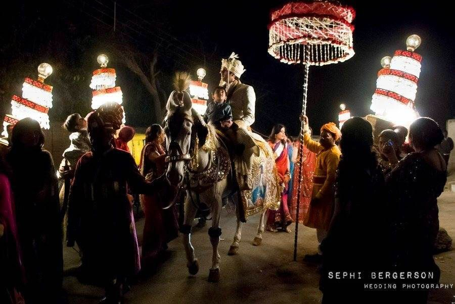 A baraat procession during a Hindu punjabi wedding. I wanted to get the shot of the people carrying the lamps and had to work without a flash for that or I would have changed the image completely and loose the entire feel of the night lit by the lanterns. The light falling on the bridegroom and his horse came out just the way I had hoped. (Karishma & Rishabh's wedding in Delhi)