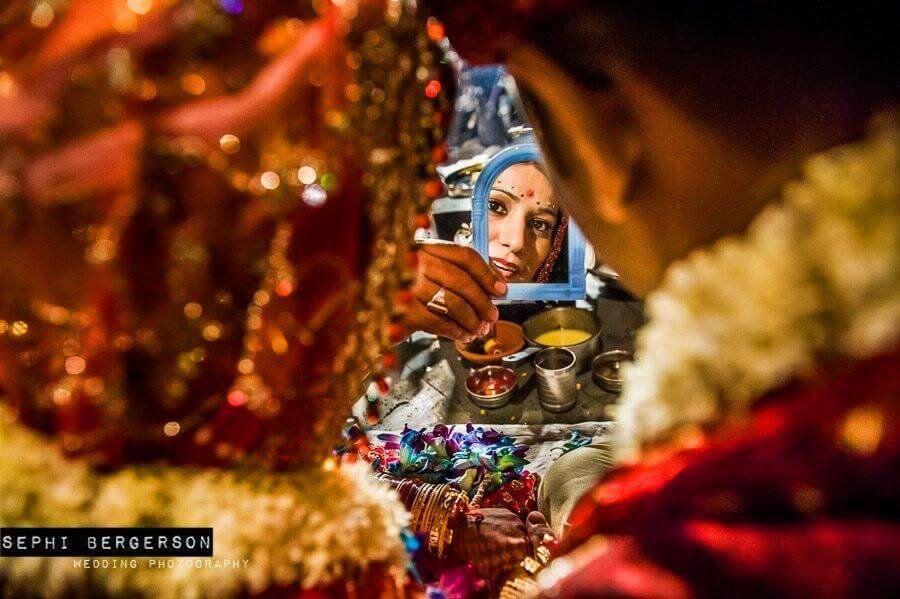 During a Kashmiri Pundit wedding I saw the priest holding a plastic miror in his hand. I had a feeling it was going to be used for the bride and groom to look at each other so quickly positioned myself just behind them and was ready as the priest held his hand out just for a second in front of the couple. It is one of those shots that one can never get unless you wait for them to happen. (Anuradha & Nikhil's Kashmiri Pundit wedding in Delhi)