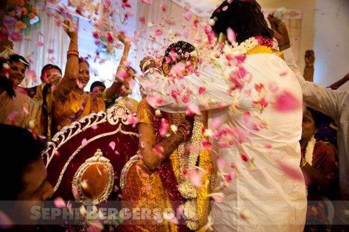 The groom gives his wife a gold neckless called Taali as the guests shower them with flower petals.