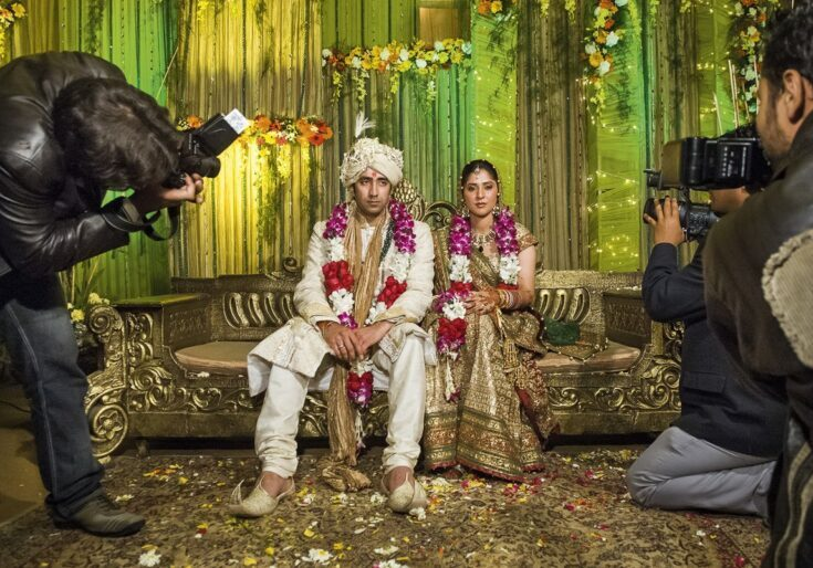 The couple are seated together on an elevated platform and the traditional photographers take their first picture together before the wedding. After a minute or two even the most patient couple could be tired of posing. Punjabi wedding in Delhi, 2008