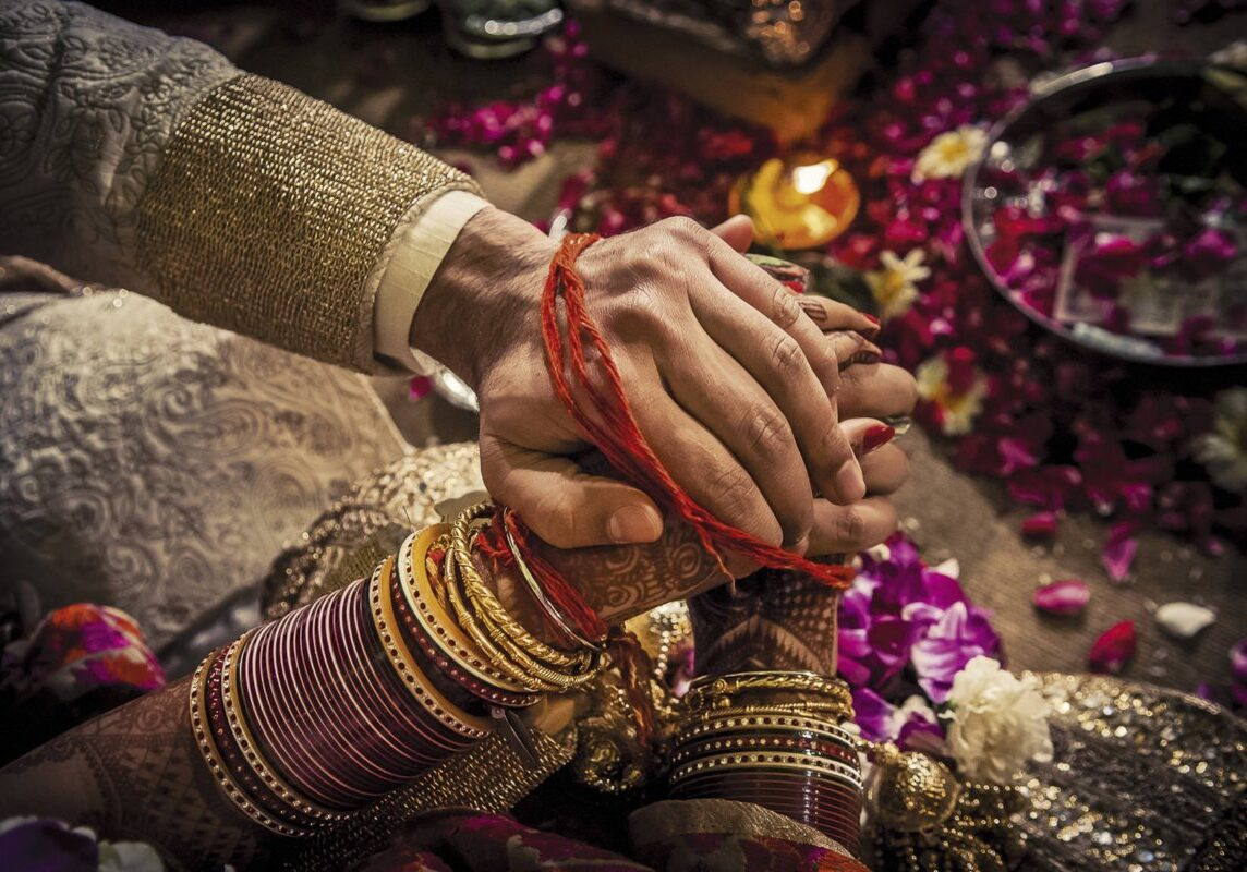 """The panigrahana (""""accepting the hand"""") ritual of a Hindu wedding, where the groom accepts the bride by taking her right hand in his. This might be the first time the couple has physically touched one another. During this ritual the husband accepts his bride and vows to her and her parents that he will take care of and protect his bride for the rest of her life. Delhi 2008"""